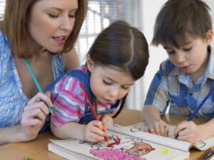 stay at home mom helping children color
