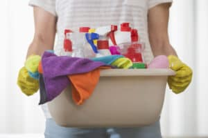woman holding basket of cleaning supplies