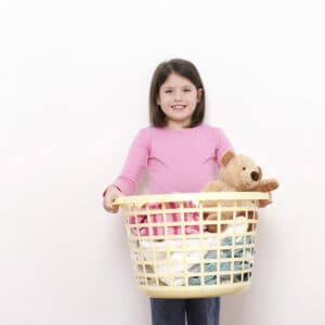 young girl holding laundry basket of clothes and toys