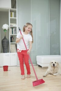 young girl sweeping the floor