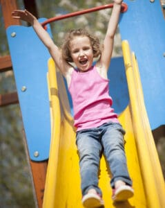 girl going down the slide at a park