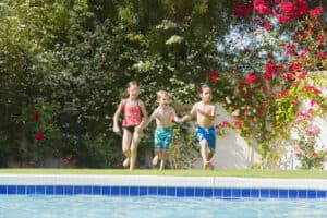 kids jumping into a pool in the summer