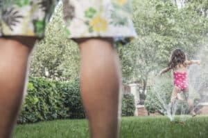 little girl running through sprinkler