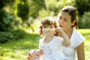 mother and son blowing bubbles together in summer