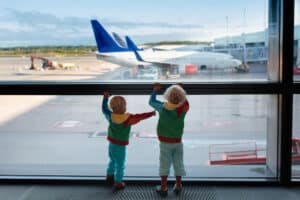 toddler at an airport with airplane background