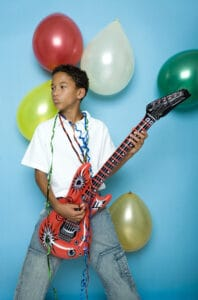 boy playing guitar at birthday party