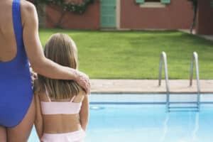 mother wearing swimsuit in pool with daughter