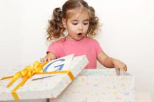 toddler opening birthday present from gift guide for toddlers