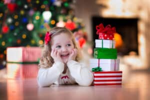 toddler smiling waiting to open Christmas presents from the gift guide for toddlers