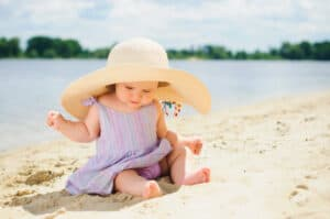 baby girl in sunhat playing in the sand at the beach
