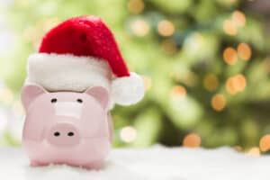 piggy bank wearing a Christmas hat in front of a Christmas tree