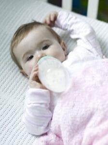 baby taking bottle in crib