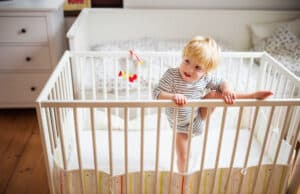 toddler trying to crawl out of the crib